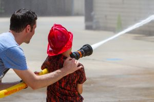 Picture of child with father, spraying fire hose